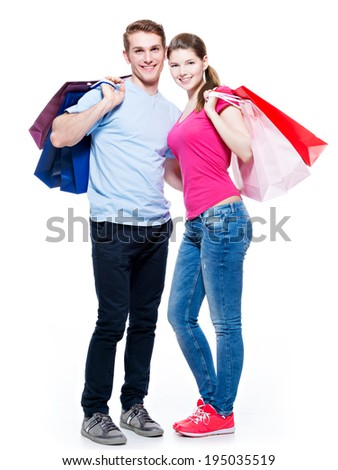 Full portrait of the happy young couple with shopping bags - isolated on white background. - stock photo