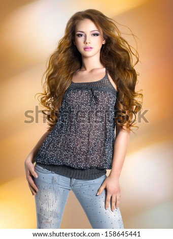 Full portrait of the young sexy beautiful woman with long curly hairs posing at studio - stock photo