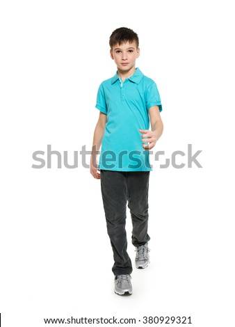 Full portrait of walking teen boy in blue t-shirt casuals  isolated on white background.   - stock photo