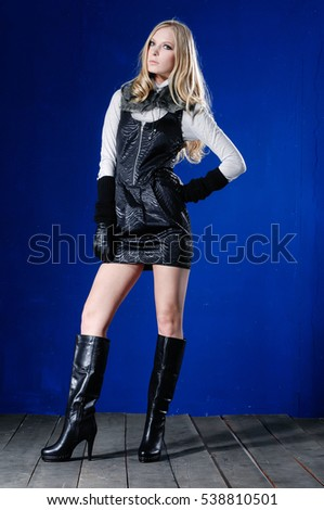 Full portrait of young beautiful woman in gloves, boots standing posing-blue background