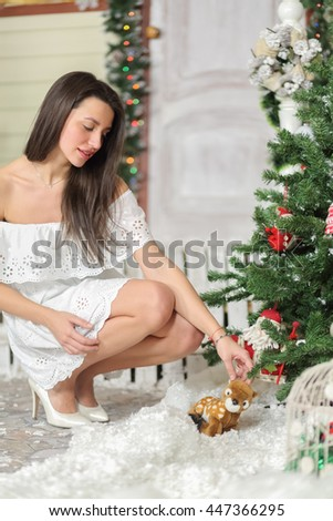 Full portrait of young woman sitting on squatting in courtyard of fake home and picks up toy from snow. Christmas interior studio - stock photo