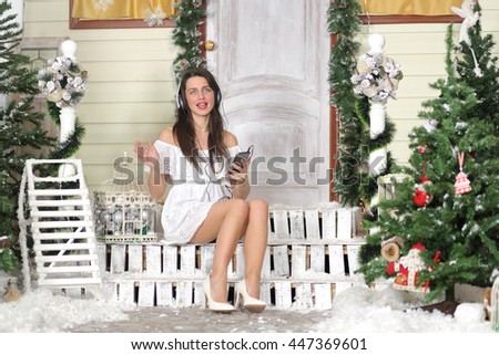 Full portrait of young woman sitting on threshold of fake home and listening music in headphone, sing. Christmas interior studio - stock photo