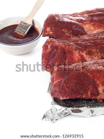 Full Racks of Uncooked, Full Racks of Baby Back Ribs With bowl of Spicy BBQ Sauce and Basting Brush Ready to be Baked or Grilled, on white background - stock photo