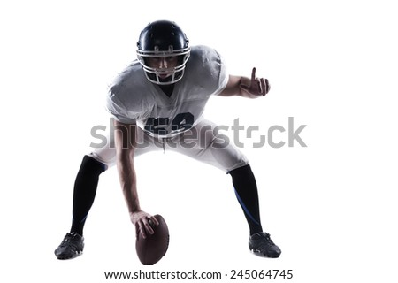 Full readiness.  American football player getting ready before throwing ball while standing against white background  - stock photo