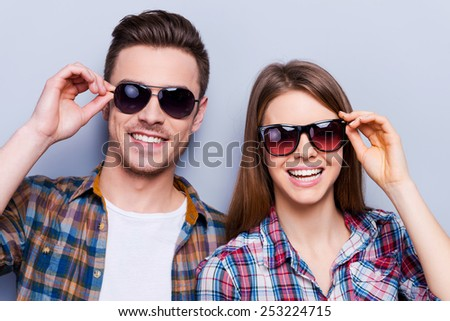 Full ready for summer! Beautiful young loving couple adjusting their sunglasses while standing against grey background - stock photo
