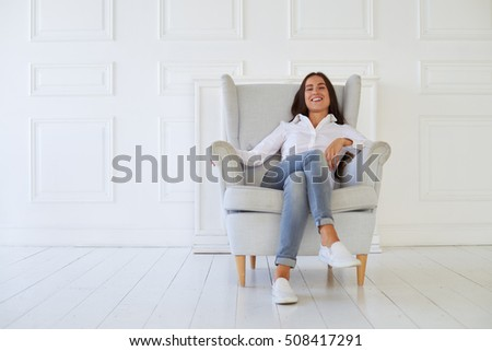 Full relaxation of pleasant delighted positive woman sitting in the armchair and smiling