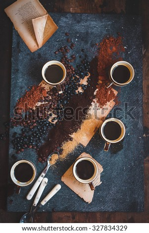 Full roast variety coffee beans piled on a rough rustic stone surface with a five cups of freshly brewed espresso coffee with frothy bubbles, top view. Rustic dark style. - stock photo