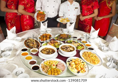Full rounded table of Chinese food with chef and waitress behind - stock photo