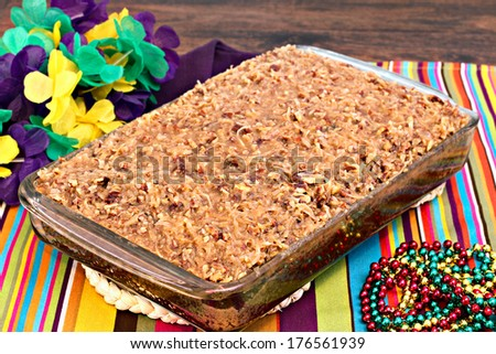 Full sheetcake of a cajun cake with praline topping in a mardi gras setting. - stock photo
