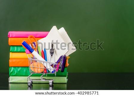 Full shopping cart with books near empty green chalkboard. - stock photo