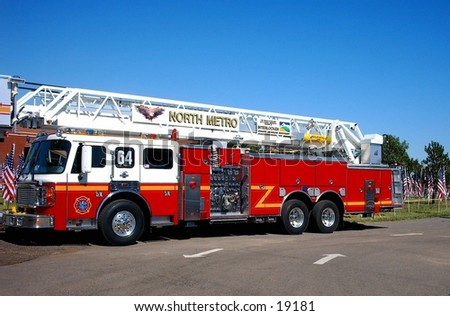 Full side-view image of a Ladder  firetruck against a blue sky.
