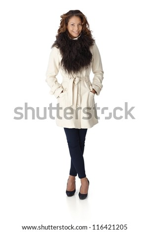 Full size autumn portrait of pretty young woman in white coat with fur around neck.