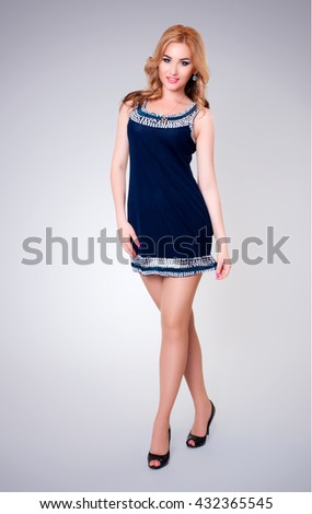 Full size portrait of attractive caucasian blonde woman in blue dress in studio - stock photo