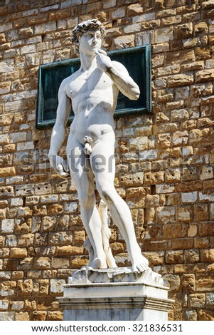 Full-sized replica of the original statue of David (by Michelangelo) in front of the Palazzo Vecchio on the Piazza della Signoria, Florence, Italy. Florence is a popular tourist destination of Europe. - stock photo
