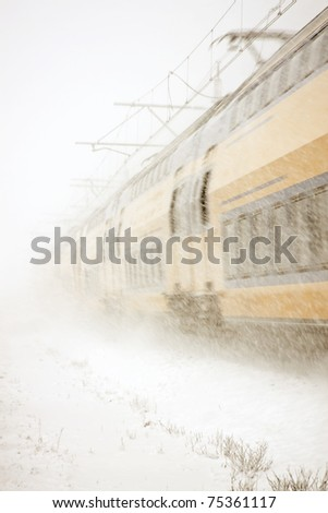 Full speed train driving in snowstorm in the countryside from the Netherlands - stock photo