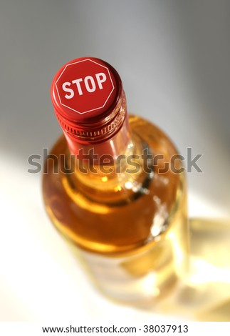 full spirits bottle with stop sign on top - stock photo
