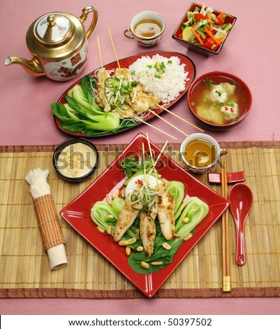 Full Table Setting Of Asian Chicken Skewers With Short Soup And Vegetables