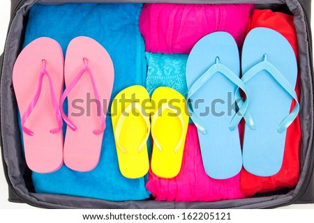 full travel suitcase with clothing and flip-flops - stock photo