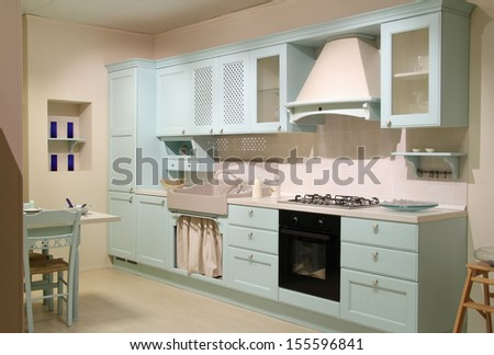 Full view of a country style cyan kitchen with complete furniture.  - stock photo