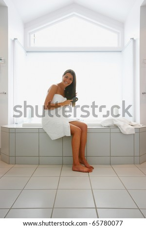 Full view portrait of woman wrapped in towel brushing hair - stock photo