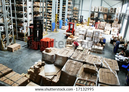 Full warehouse with forklifts and lots of packages - stock photo