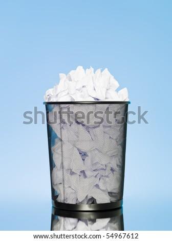 Full wastebasket on blue background - stock photo