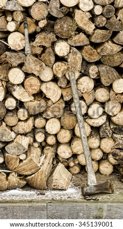 Full woodshed in winter with a splitting maul and hatchet.