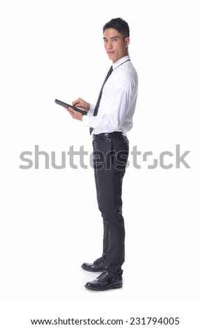 Full young business man using tablet posing in studio
