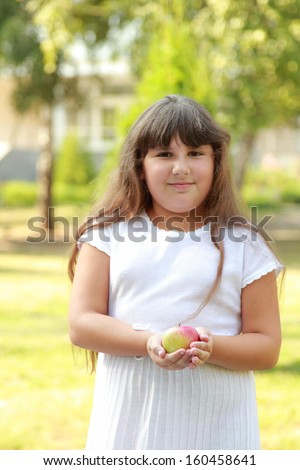 Full young girl in a white dress standing in a summer park and holding an apple - stock photo