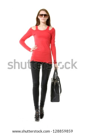 Full young woman in sunglasses with handbag. Walking in studio - stock photo