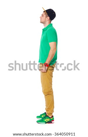 Fullbody profule portrait of young man standing in studio isolated on white.