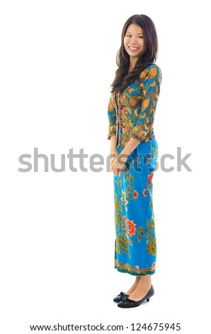 Fullbody southeast Asian woman in traditional batik kebaya clothing standing, isolated white background - stock photo