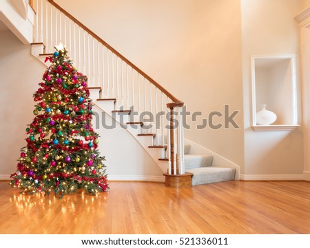 Fully decorated Christmas on wooden floor with staircase in background