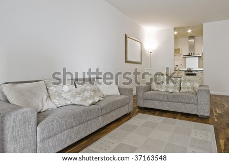 fully furnished open plan living room with two linen sofas - stock photo