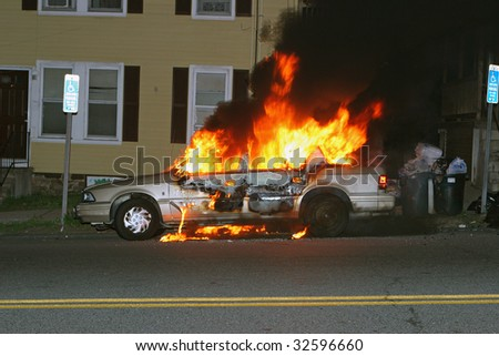 Fully involved vehicle on the side of the road - stock photo