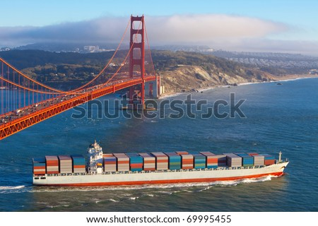 Fully laden container cargo ship leaving San Francisco bay under the Golden gate bridge in the late afternoon - stock photo
