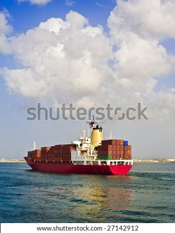 fully loaded cargo ship leaving the port - stock photo
