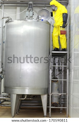 Fully protected engineer in uniform,mask,gloves ,boots technician with sample in plastic container controlling industrial process in factory  - stock photo