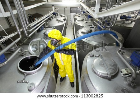 fully protected in yellow uniform,mask,and gloves technician filling large  silver tank in factory - stock photo