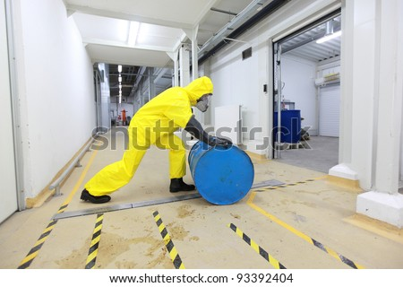 fully protected in yellow uniform,mask,and rubber gloves and boots worker,rolling the barrel with toxic substance - stock photo