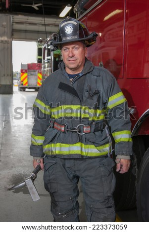 Fully Uniformed FireFighter Holding Gear standing in front of fire truck portrait - stock photo