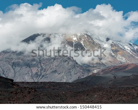 Fumarole field on the slopes of volcano Tolbachik, on background volcano Ostry Tolbachik in the clouds  - Kamchatka, Russia