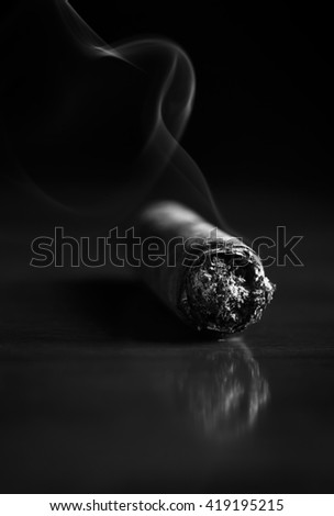 Fuming Havana cigar on a wooden table (b&w) - stock photo