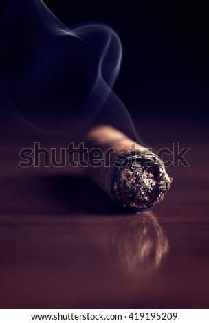 Fuming Havana cigar on a wooden table (with copy space) - stock photo