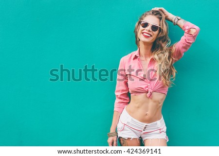 Fun and colorful. Young pretty happy woman in shorts posing against green wall. - stock photo