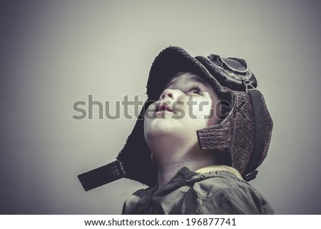 fun and funny child dressed in aviator hat and goggles - stock photo