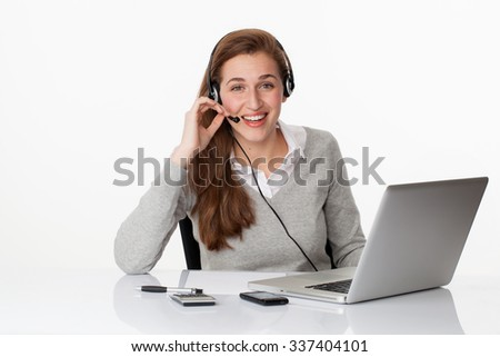 fun at work concept - thrilled young female manager communicating about good news on headset and pc, studio shot,white background