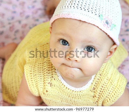 Fun baby in hat with blue eyes and yellow dress looking in camera. Closeup portrait - stock photo