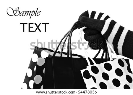 Fun black and white photo of gloved hand with shopping bags.  Close-up with shallow dof.  Copy space included. - stock photo