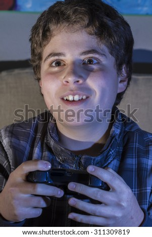 Fun boy with joystick playing computer game at home. - stock photo
